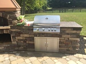 outdoor kitchen with brick oven fireplace with grill